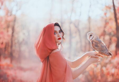 mystical pagan woman with covered head in peach scarf in forest, holds cute little barn owl. lady with dark curled hair, bright make-up and fair pale skin, daughter of autumn forest caring for bird Banco de Imagens