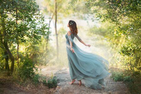 Märchenprinzessin in hellem sommerblauem Türkiskleid auf breitem Weg und geht in Richtung Wind, anmutiges Tanzmädchen im Bild einer Blume mit fliegendem langen Saum des Kleides, Nymphe aus hellgrünem Wald Standard-Bild