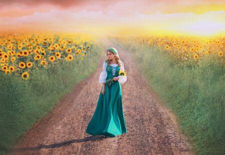 charmante fille en robe longue verte avec une chemise blanche marche le long de la route, une dame aux tresses blondes tient des fleurs jaunes dans les mains, la beauté rurale rentre du champ, photo d'art avec un ciel rose au coucher du soleil