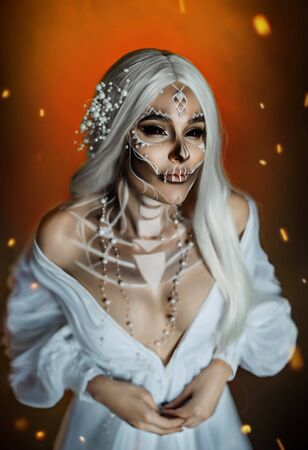 woman with creative professional makeup Calavera Catrina. The image of a gray-haired witch in a white, vintage, wedding dress. Unusual make-up with beads pearls. Black scleral lenses for the whole eye Banque d'images - 129140747