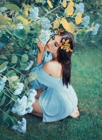 A young woman sits on her knees and hugs blooming blue hydrangeas in a summer garden with love and tenderness. Forest nymph in a short light dress and in a golden wreath on dark hair. Open shoulders