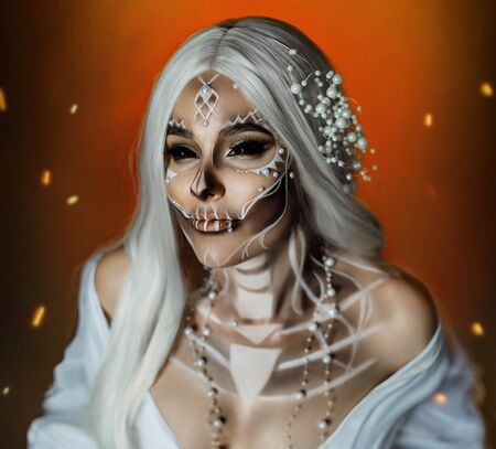 woman with creative professional makeup Calavera Catrina. The image of a gray-haired witch in a white, vintage, wedding dress. Unusual make-up with beads pearls. Black scleral lenses for the whole eye Stockfoto