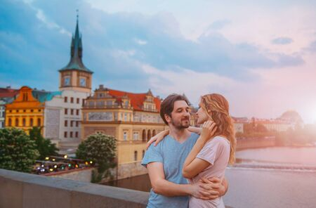 Loving, young couple hugging on a bridge with a view of the old city of Prague. Background of multi-colored, vibrant houses, cloudy blue sky. Sun flare and vanilla flash. Walk on the roof.