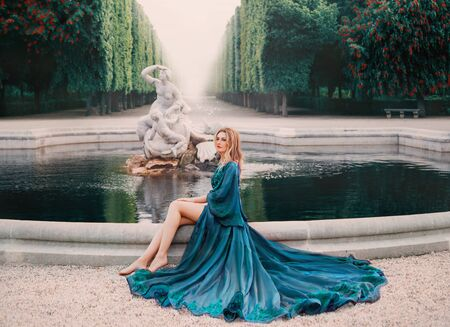 A young blonde woman sits near an old royal pond with ancient statues with a fountain and dreams. Queen in a luxurious blue silk peignoir with a long train and wide sleeves. Art processing Stockfoto