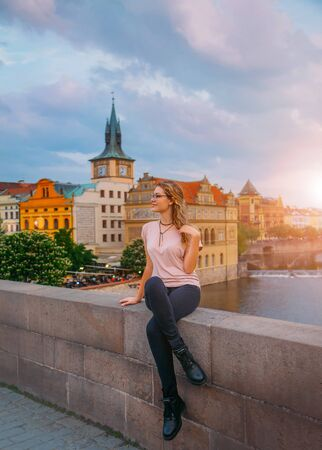 woman sits on a bridge over a river and enjoys the sunset with a smile on her face. Tourist in the old town of Prague. View of multi-colored beautiful houses and buildings. blue jeans, pink t-shirt