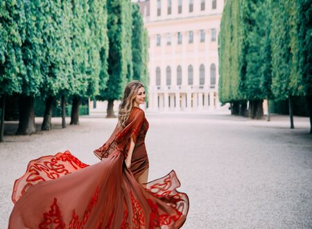 A happy, cheerful woman in a red evening dress runs and looks around with a smile on her face. Blond hair and a luxurious train of silk dress fluttering in the wind. Background beautiful garden.