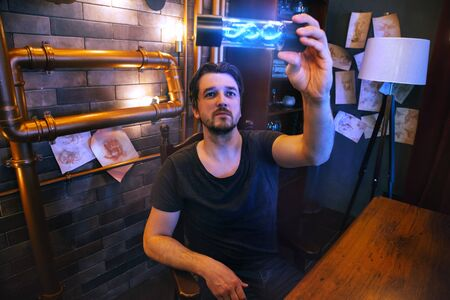 Portrait of a young man in a steampunk scientist's office. The doctor holds in his hands a flask with a dna structure that glows in blue. Handsome bearded intelligence spy guy.