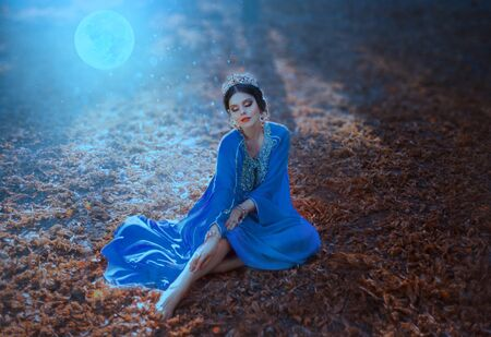 Young woman with the moon. Night autumn landscape. The Eastern Queen in a blue dress sits on the ground covered with fallen leaves in the moonlight. Tales of Shikhirizada 1001 nights. Art photography Stockfoto