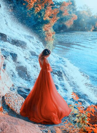 A mysterious young sad woman stands on the riverbank near a waterfall, in a red, long dress and dreams. Background autumn landscape, yellowed trees. Shooting from the back, without a face, rear view. Stockfoto