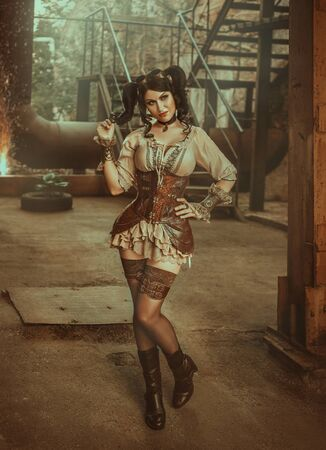 A cheeky young woman in a creative suit in the steampunk style stands against the backdrop of an old building with sparks and rusty pipes. Chic coquette plays with her hair with ponytails. Warm colors 写真素材