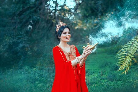 A woman in red luxurious oriental with a golden Aladdin lamp calls Gin. Positive emotions, the queen smiles. Magic and miracle. Smoke from a jug. Background summer and green trees. Art photography 写真素材