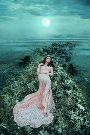 A pretty woman lies in a boat that is decorated with white flowers, herbs willow . Sleeping beauty in a luxurious pink dress with a train floats on the river in the moonlight. Dramatic sky with clouds