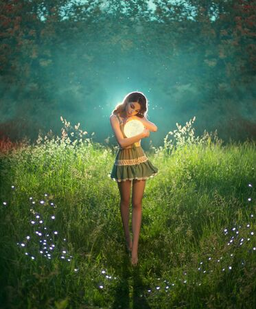 Attractive, cute woman holds the moon in her hands. The princess of the universe in a short dress hugs a luminous planet. Walk in a dream. Green evening summer forest. Fairytale landscape with stars Banque d'images - 129956849