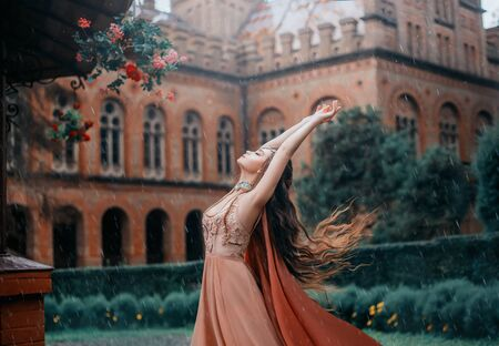 Lady with a pretty face, stands under the rainy sky and reaches out to meet the drops. Young magician in a orange dress with a cape near the castle. Dance with the wind, long hair flying, fluttering. 스톡 콘텐츠
