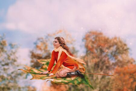 A cheerful woman sits on a maple leaf and flies in the sky, her hair fluttering. The concept of freedom and independence. Casual wear orange sweater, yellow scarf. Autumn landscape on the background.