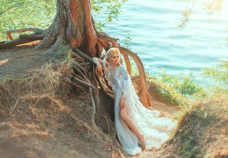 Luxurious blonde woman in a white dress with a long royal cape with feathers. Queen Swan stands near a tree with huge roots on the river coast. Background summer nature landscape, warm green colors.