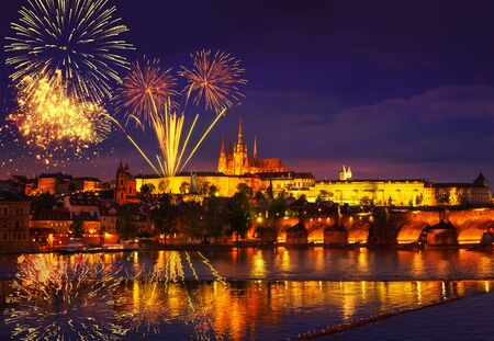 Colorful massive fireworks show over the Prague Czech Republic. Celebration concept, New Years Eve 2020. Panoramic shot of the night city with lights and reflection in the water. December 31