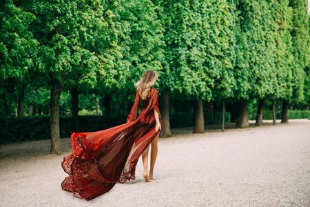 tall woman in a red silk dress with a long train that flutters in the wind. Medieval fashion of luxurious wide-sleeve peignoirs. Summer day. Happy valentines day. The girl goes to meet her beloved.