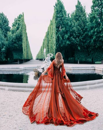 Mysterious queen in a red transparent long peignoir with a train. Attractive blond woman with her hair walks in a luxurious garden with a fountain. Background of tall cut green trees, like a wall.