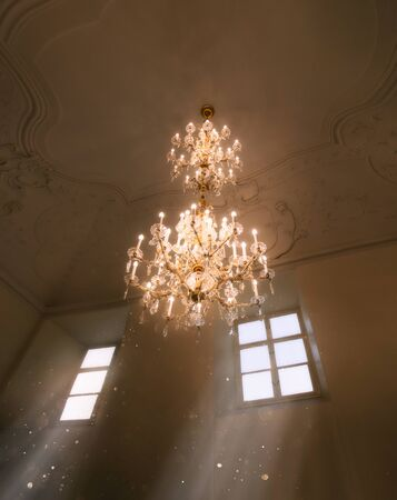 A fabulous room with a luxurious crystal, antique chandelier on the ceiling with lace ornament and vintage plaster stucco molding. The magic light of the sun pours soft rays from the window