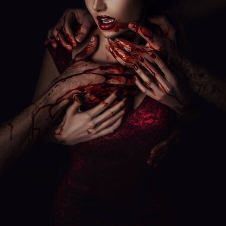 vampire in blood and drops. A woman in a passionate embrace of mans hands. Backdrop mystic dark room. Gothic queen in a red dress. Bloodthirsty couple of lovers. Lady without face, lips and chest