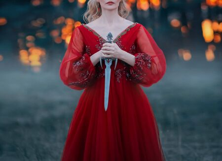 A mysterious blond woman holds a dagger of beautiful Gothic design in her hands. Fantasy lady soldier fashion warrior in a dark forest. Shooting without a face, only lips and hands. Cut off the head 版權商用圖片