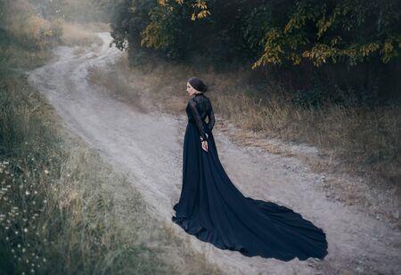 Silhouette der gotischen Dame aus dem alten Fantasy-Horrorfilm. Spaziergänge entlang der Straße im Herbstwald. Schöner Vampir. Schwarzes Vintage-Kleid mit langer Schleppe. Design Alte dunkle Mode. Halloween-Feiertag Standard-Bild