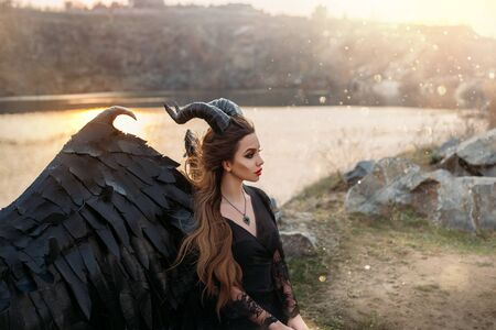 Fabolous character dark fairy, fallen angel demon hell. Woman in carnival gothic latex costume with horns. Black leather wings. Fashion design. perfect skin. Magic sun rays light. flying long hair