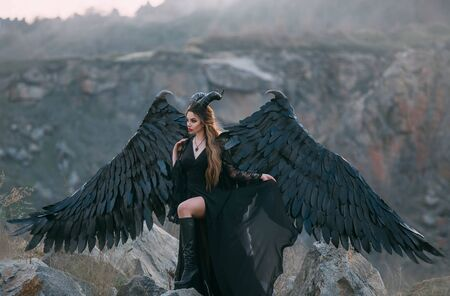 Fantasy dark magician in a black dress with huge wings and horns. Gothic model Transformation of mythical goddess Gamayun syrin. Fabolous mountains and cliffs. image outfit for Halloween party