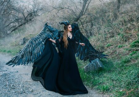 Fantasy dark fallen angel in a black dress with huge wings and horns. Gothic queen walks in the autumn forest of trees. Cold spring nature. An image of outfit for a Halloween party. Carnival costume