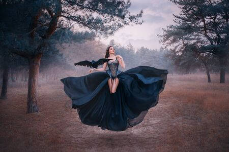 attractive seductive sexy fantasy witch levitating in air. Woman with black raven on hand. wings bird. silk dress flutters. Gothic vintage style design. Cold winter forest nature backdrop with fog 写真素材