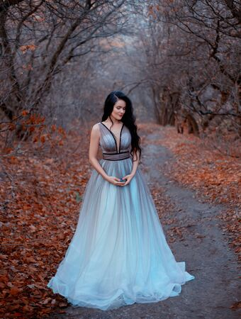brunette woman with long hair walks in autumn forest of November. Background black bare trees and fallen orange leaves. Queen enjoys nature. Royal luxury puffy turquoise dress. Graduation Party Image Stock Photo