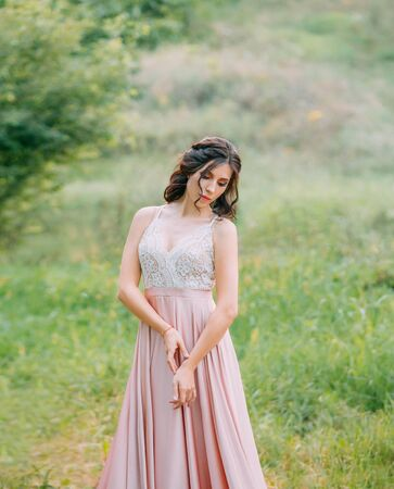 Cute attractive brunette woman enjoying nature in delicate elegant pink silk dress with white lace top. Image for party graduation prom ball stylish evening outfit celebration. Fashion glamor summer Banco de Imagens