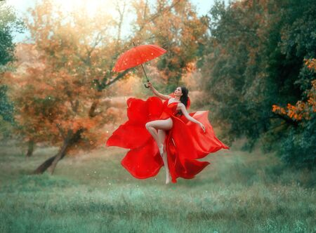 Happy pretty brunette woman in red dress with an umbrella flies in air. Long bare legs in dance. Art photography levitation. Silk fabric waving like flower. Backdrop autumn landscape, bright colors.
