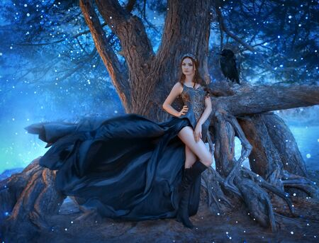 Dark queen with raven stands near tree roots in night Gothic forest. Long legs creative black dress, flying waving silk train. attractive seductive vampire. Magic fireflies, sparks blue fog