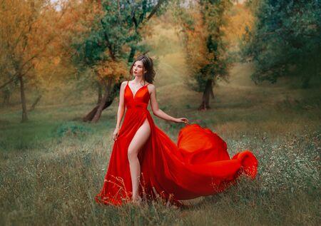 赤い緋色のドレスを着たグラマラスなブルネットの女性は、彼女の足に非常に高いスリットを着ています。 写真素材