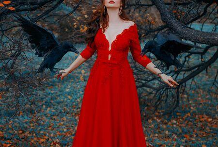 Misteriosa mujer de labios rojos con un lujoso vestido de seductor escote profundo. Bruja conjura convoca cuervos negros. Dama glamorosa con pájaros. Otoño paisaje de cuento de hadas. Disparos sin rostro.