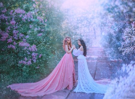 concept of change season winter and spring meet. Stylish luxury vintage design gown long train. Two women model blonde and brunette hugging. Idea inspiration family photoshoot. Fabulous snow nature