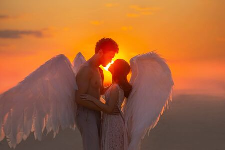 Mysterious dark silhouette two angles meet at sunset hug. Lovers muscular man and tender woman marry in heaven. concept love fidelity. warm color orange sky red sun light sun. Carnival costume wings Imagens