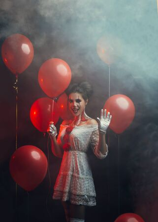 portrait cute young woman crazy smiling face clown in white costume stands backdrop dark gothic room holding red balloons waved hand. art creative bright halloween make-up hairstyle. Fog smoke party