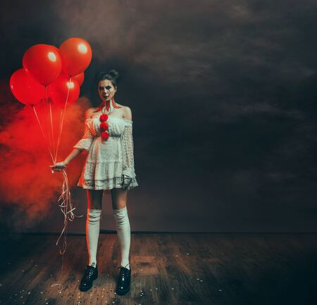portrait cute young woman with scary face clown grimm in white old dress stands in backdrop dark black gothic room holding red balloons. art creative makeup. Fog smoke free space text. lady ghost