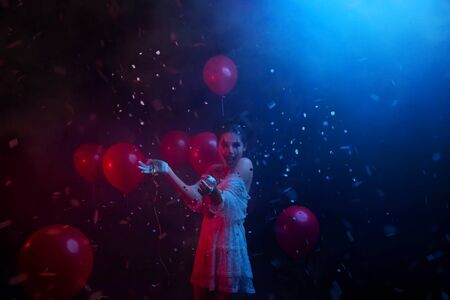woman in clown costume laughs fun at party with neon red blue light, explodes spangles falling serpentine fall. happy joy Smile on pretty greasepaint face creative art make-up. Halloween animator Stock Photo