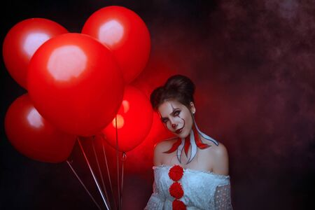 portrait cute young woman crazy smiling face clown in white costume stands backdrop dark gothic room holding red balloons evil eyes. art creative bright halloween make-up hairstyle. Fog smoke party