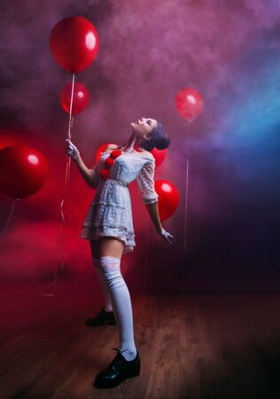 Happy funny sexy joy Woman clown in old costume knee high black retro boots, creative art bright mad makeup face, hairstyle two bun. Backdrop black gothic mystic room fog smoke, hold red balloon. Stock Photo