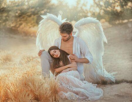 Los hombres ángel de la guarda protege y abraza a la mujer joven. Bella durmiente color pastel vintage, sueño milagroso. Fabulosa naturaleza de otoño amarillo cálido viejo. Luz brillante del brillo del sol. Ala de diseño de traje blanco creativo Foto de archivo