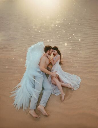Men guardian angel protects and hugs young woman. Sleeping beauty vintage pastel color, miracle dream. Fabulous old warm sand desert nature. Bright sun shine light. Creative white suit design wing