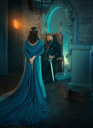 La reina de la belleza de lujo se alejó. ropa creativa real medieval. La dama sostiene la daga gótica hacia atrás. Capa de manto azul. Telón de fondo antigua habitación retro. El rey de los hombres adultos fuertes se sienta en el trono. Conspirador peligroso