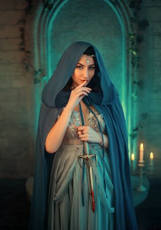 Luxury beauty elf Queen medieval royal creative clothes holds gothic dagger stained blood. Blue silk dress, cloak hood silver tiara. Backdrop old retro castle room. Dangerous Strong power conspirator