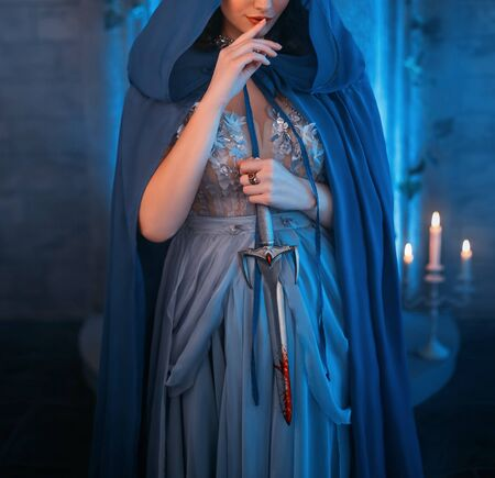 Luxury beauty elf Queen medieval royal creative clothes holds gothic dagger stained blood. Blue silk dress, cloak hood silver tiara. Backdrop old retro castle room. Dangerous Strong power conspirator 版權商用圖片
