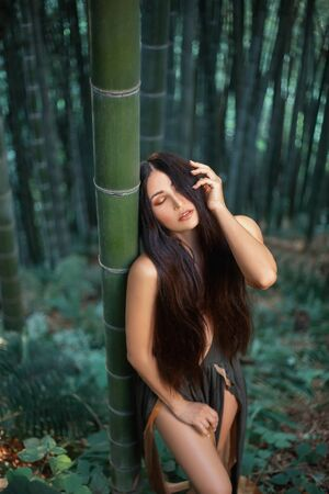Pretty sexy Amazonian relax silence in bamboo forest. hand touch long hair, eyes closed. nymph dress with deep neckline. art Backdrop summer tropics nature botanical garden Georgia. spring vacation.